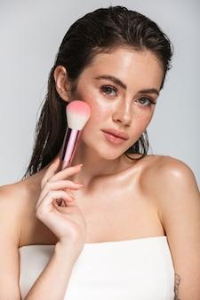 Retrato da beleza de uma jovem atraente e sensual com cabelo comprido morena molhada em pé isolado em uma cor cinza, usando pincel de maquiagem