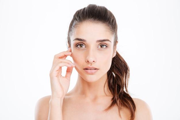 Retrato da beleza de uma jovem atraente tocando seu rosto sobre uma parede branca