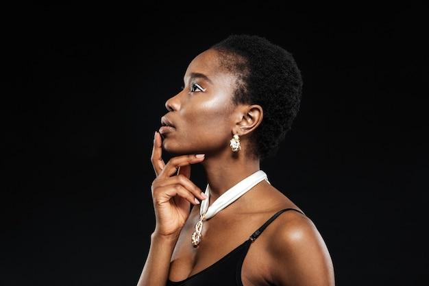 Retrato da beleza de uma jovem bela mulher étnica isolada na parede preta