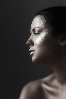 Retrato da beleza de uma jovem bonita com maquiagem de fantasia e brilho de pele escura no rosto