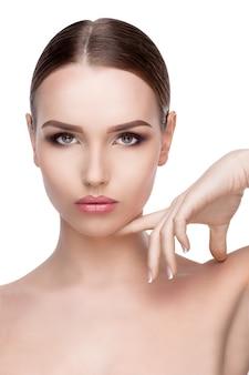 Retrato da beleza de uma jovem com uma pele limpa, perfeita e fresca de perto isolado na parede branca
