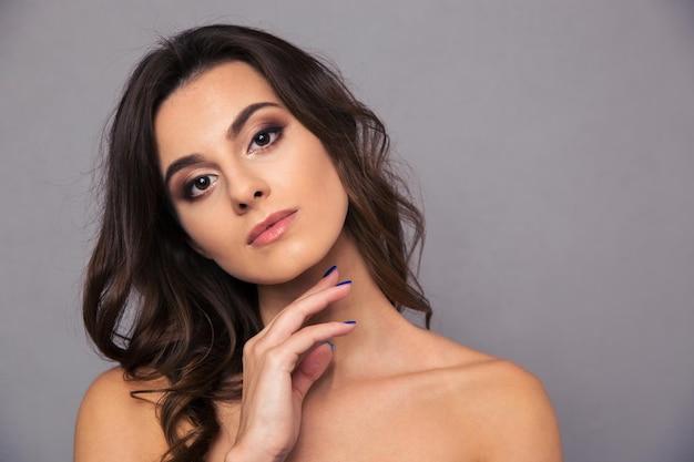Retrato da beleza de uma jovem cuidando da pele em uma parede cinza