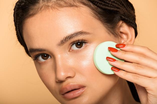 Retrato da beleza de uma jovem e atraente mulher de topless isolada sobre uma parede bege, removendo a maquiagem com um algodão