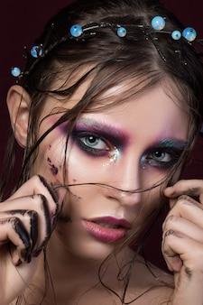 Retrato da beleza de uma jovem garota com maquiagem criativa de moda e grinalda tocando seu cabelo. olhos esfumados coloridos. maquiagem moderna