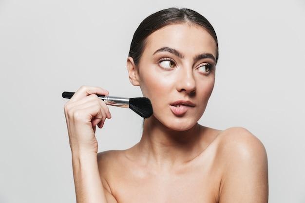 Retrato da beleza de uma jovem morena atraente e saudável, de pé isolado, aplicando maquiagem com um pincel