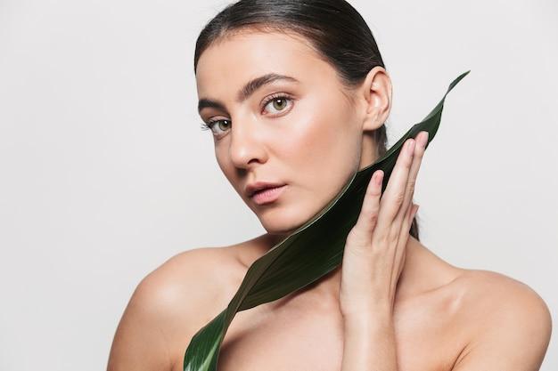 Retrato da beleza de uma jovem morena atraente e saudável, de pé isolado, posando com folha verde tropical.