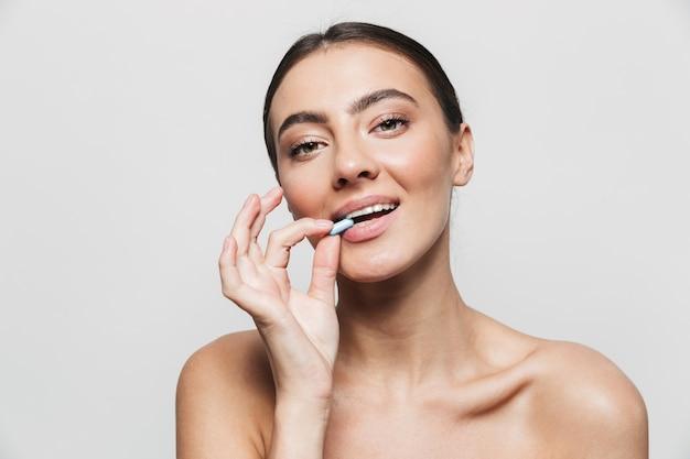 Retrato da beleza de uma jovem morena atraente e saudável, de pé isolado, segurando a pílula na boca