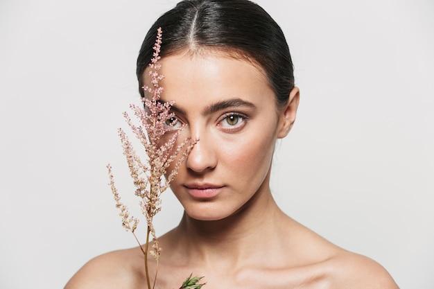 Retrato da beleza de uma jovem morena atraente e saudável em pé isolado segurando uma planta de flor perto do rosto