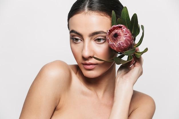 Retrato da beleza de uma jovem morena atraente e saudável, isolada, segurando uma flor no rosto