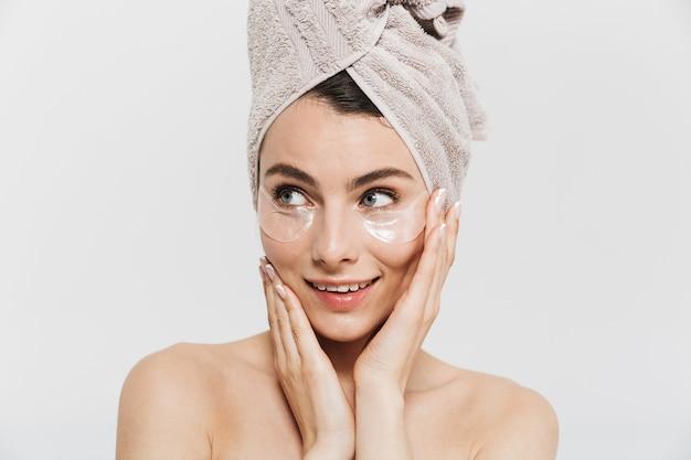 Retrato da beleza de uma jovem morena atraente em pé isolado sobre uma parede branca, usando uma toalha na cabeça, aplicando tapa-olhos cosméticos