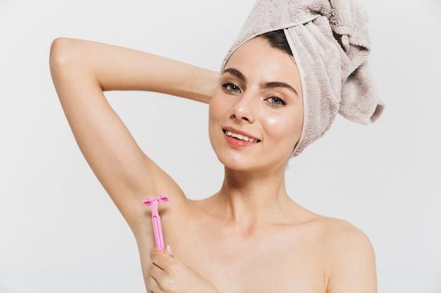 Retrato da beleza de uma jovem morena atraente em pé isolado sobre uma parede branca, usando uma toalha na cabeça, raspando a axila