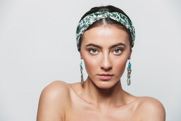Retrato da beleza de uma jovem mulher bonita em topless usando bandana e brincos isolados