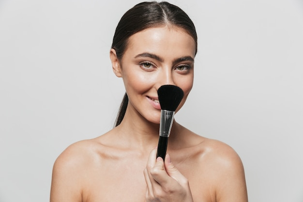 Retrato da beleza de uma jovem mulher de topless isolada, segurando o pincel de maquiagem