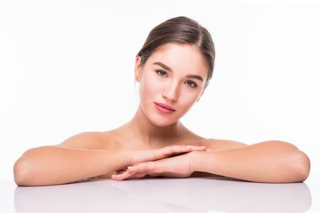 Retrato da beleza de uma jovem mulher meio atraente nua com a pele perfeita, rindo e olhando para a câmera na parede branca