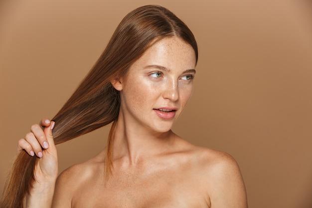 Retrato da beleza de uma jovem sensual de topless com longos cabelos ruivos posando, brincando com seu cabelo isolado sobre uma parede bege