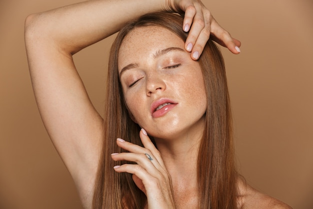 Retrato da beleza de uma jovem sensual de topless com longos cabelos ruivos posando, segurando o rosto de mãos dadas, isolado sobre uma parede bege