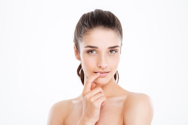 Retrato da beleza de uma jovem sensual tocando seu lábio sobre uma parede branca