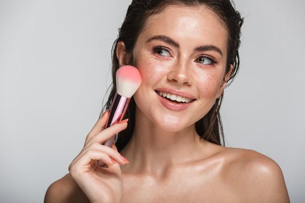 Retrato da beleza de uma jovem sorridente atraente e sensual com cabelo comprido morena molhada em pé isolado em uma cor cinza, usando pincel de maquiagem