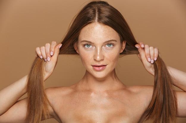 Retrato da beleza de uma jovem sorridente de topless com longos cabelos vermelhos posando, brincando com seu cabelo isolado sobre uma parede bege