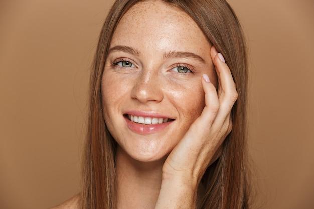 Retrato da beleza de uma jovem sorridente de topless com longos cabelos vermelhos posando, segurando o rosto de mãos dadas, isolado sobre uma parede bege