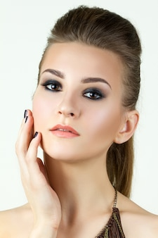 Retrato da beleza de uma jovem tocando seu rosto