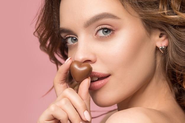 Retrato da beleza de uma linda garota em ação para comer um doce de chocolate sobre o fundo rosa do estúdio