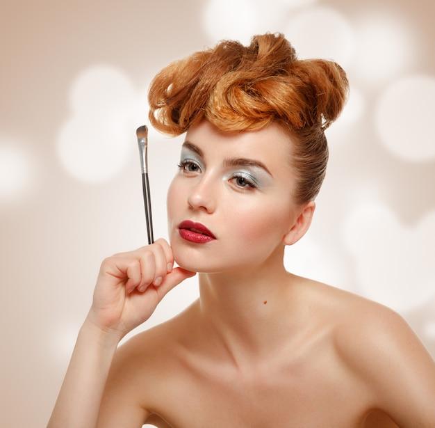 Retrato da beleza de uma linda mulher com pincel para maquiagem
