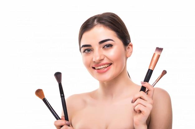Retrato da beleza de uma linda mulher seminua bonita segurando o conjunto de pincéis de maquiagem