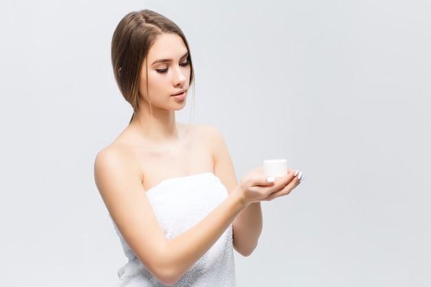 Retrato da beleza de uma linda mulher seminua olhando creme na palma da mão isolado sobre uma parede branca