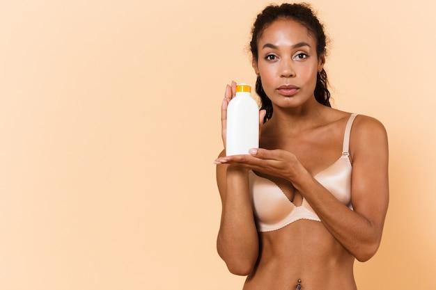 Retrato da beleza de uma mulher afro-americana usando lingerie branca, segurando o frasco com cosméticos, em pé, isolado sobre uma parede bege