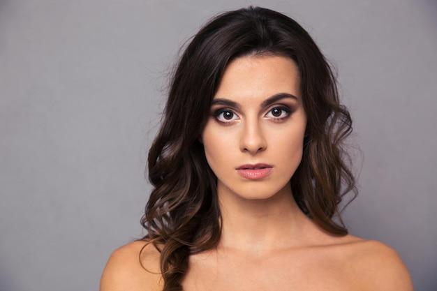 Retrato da beleza de uma mulher atraente com pele fresca sobre uma parede cinza