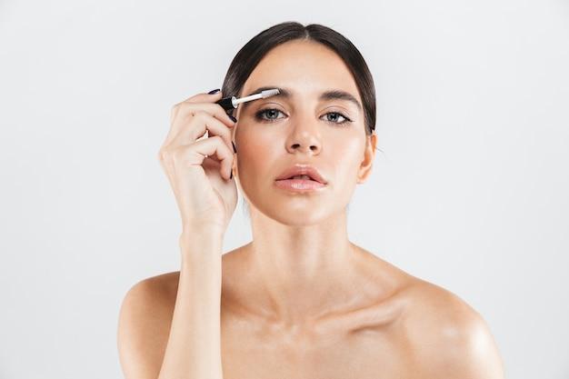 Retrato da beleza de uma mulher atraente e saudável em pé isolado sobre uma parede branca, fazendo as sobrancelhas
