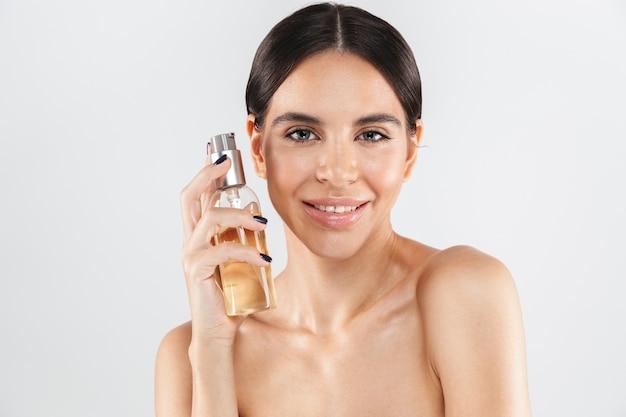 Retrato da beleza de uma mulher atraente e saudável, isolada sobre uma parede branca, aplicando óleo corporal