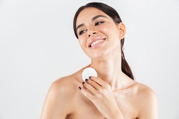 Retrato da beleza de uma mulher atraente em topless, removendo a maquiagem com um algodão isolado na parede branca