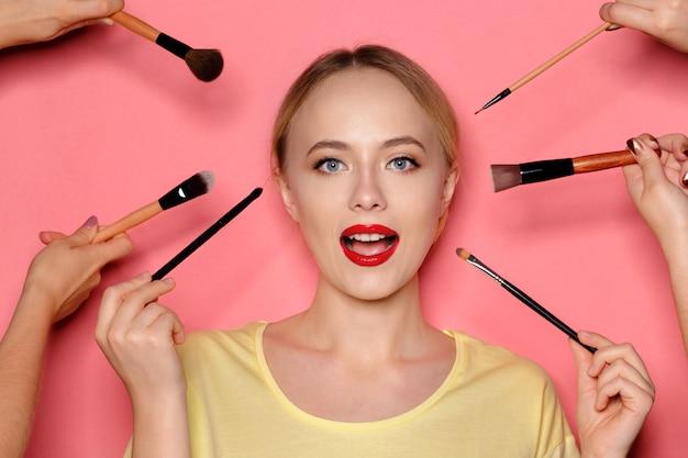 Retrato da beleza de uma mulher bonita meio nu sorridente posando com pincéis de maquiagem