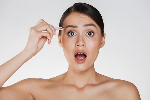 Retrato da beleza de uma mulher bonita seminua com cabelo castanho, gritando de dor enquanto arranca as sobrancelhas usando uma pinça, isolada sobre o branco