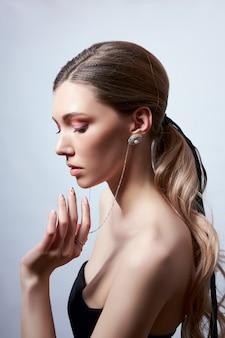 Retrato da beleza de uma mulher com cabelo comprido, brincos nas orelhas e joias caras nas mãos