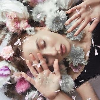 Retrato da beleza de uma mulher com flores e pétalas atrás de um vidro em gotas de chuva