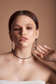 Retrato da beleza de uma mulher com jóias, brincos nos ouvidos e um colar no pescoço. pele perfeita para o rosto limpo, cosméticos naturais