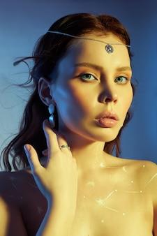 Retrato da beleza de uma mulher com maquiagem linda, brincos e um colar na menina