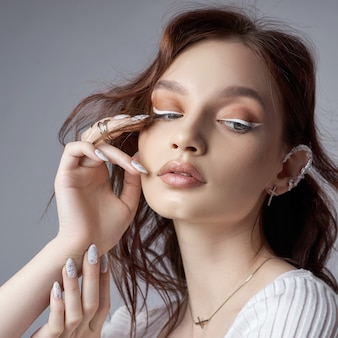 Retrato da beleza de uma mulher com maquiagem natural e unhas pintadas na mão.