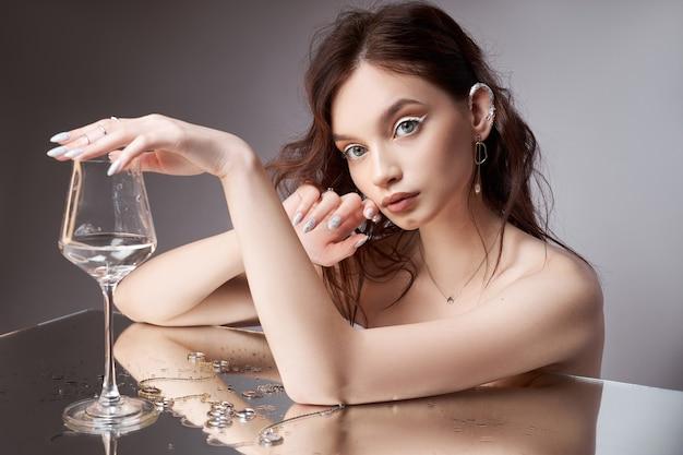 Retrato da beleza de uma mulher com um copo na mão. os anéis estão na mesa do espelho. cosméticos naturais