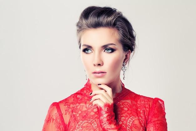 Retrato da beleza de uma mulher loira com brincos, vestido vermelho e maquiagem glamourosa em fundo branco