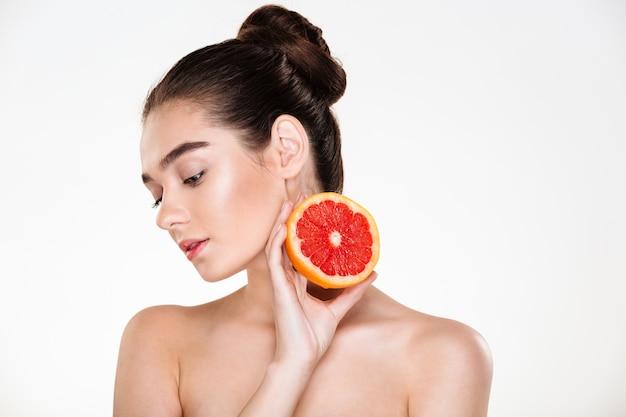Retrato da beleza de uma mulher muito feminina com pele macia, segurando a toranja suculenta perto do pescoço, tendo prazer