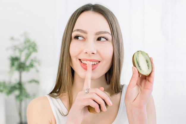 Retrato da beleza de uma mulher muito sorridente com pele saudável, mostrando o gesto de silêncio com o dedo sobre os lábios e segurando fatias de kiwi