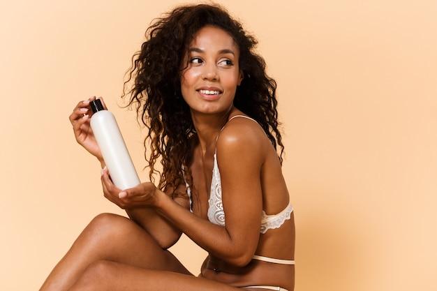Retrato da beleza de uma mulher sexual usando lingerie branca segurando cosméticos, enquanto está sentada no chão, isolada sobre uma parede bege