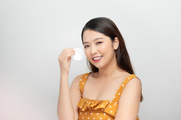 Retrato da beleza de uma mulher sorridente com pele macia e saudável, removendo a maquiagem com almofada de algodão isolada sobre fundo branco