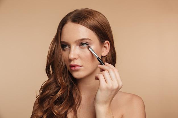 Retrato da beleza do mistério sorridente mulher ruiva com cabelos longos, olhando para longe enquanto aplica cosméticos com pincel para sombra