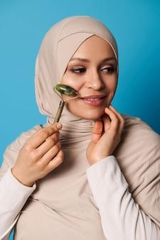 Retrato da beleza do rosto de uma mulher árabe atraente em hijab e roupa religiosa rigorosa, usando rolo de jade para drenagem linfática do rosto. tratamento de beleza.