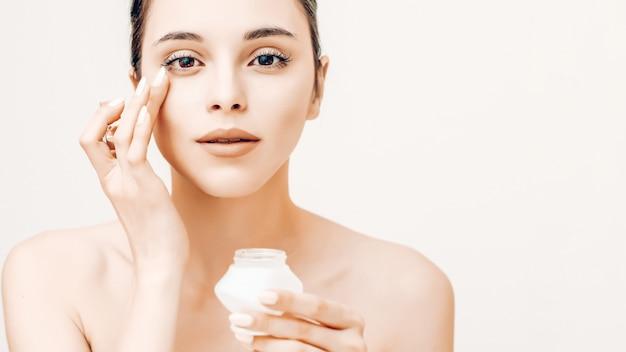 Retrato da beleza natural da jovem mulher aplicar creme no rosto